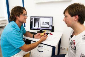 Dr. Ullmann erklärt anhand der Röntgenbilder und einem Modell eine Fußoperation